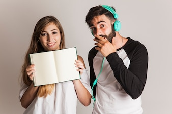 Funny couple presenting open book