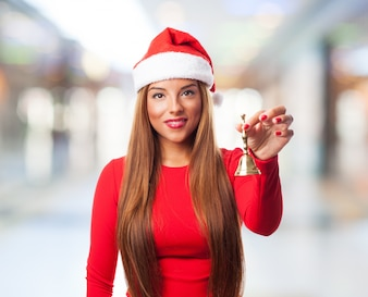 Funny woman holding a handbell on blurred background