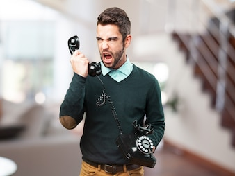 Furious man yelling at an old phone
