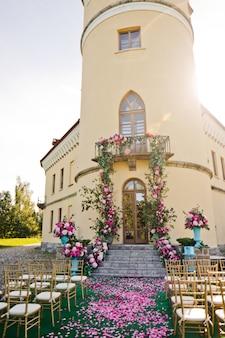緑の花輪とピンクの花が階段の上のバルコニーから垂れ下がる