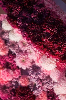 Garlands of red and pink chrysanthemums cover the wall