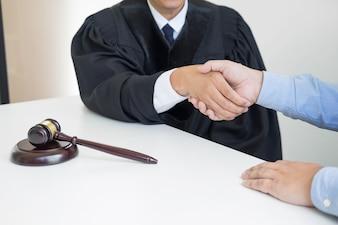 Молоток молот Правосудие на деревянный стол с судьей и клиентом, рукопожатие после консультации в фоновом режиме в зале суда, концепция адвокатского обслуживания.