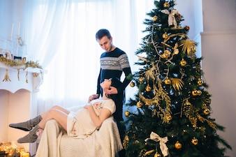 Gentle couple in Christmas waiting baby