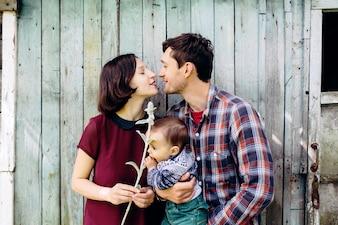屋外の赤ちゃんとポーズをとった穏やかなカップル
