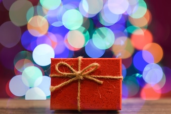 Gift box on wooden board with bokeh in the background