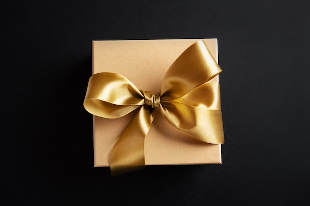 Gift box with golden ribbon on dark surface