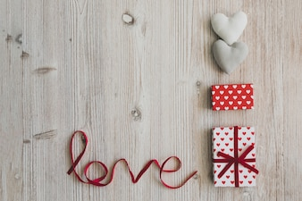 Gift boxes, two hearts and the word  love  on a wooden table