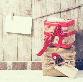 Gifts wrapped in fabric with a red bow and an envelope on a rope