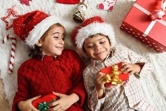 サンタの帽子を身に着けている少女と少年
