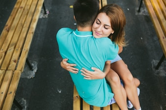 Girl and guy sitting on bench hugging