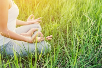 Girl doing yoga sitting in the field