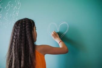 Girl drawing heart on chalkboard