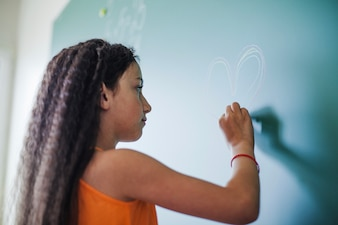Girl drawing heart on chalkboard