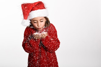 Girl dressed with winter clothes and santa hat blowing snowflakes from her hands on white background