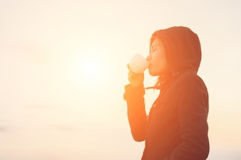 Girl drinking a cup in sunset