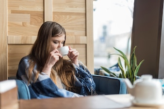 Girl drinking a tea by the window