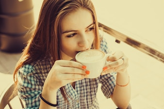 Girl drinking from a cup of coffee