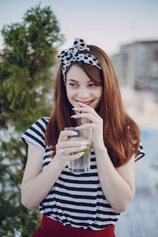 Girl drinking from a glass with a straw while smiling