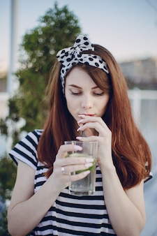 Girl drinking from a glass with a straw