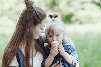 Girl eating an ice cream while her mother looks at her and smiles