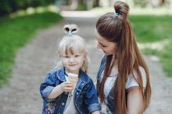 Girl eating an ice cream while her mother looks at her