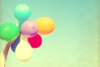 Girl hand holding multi colored balloons done with a retro vintage instagram filter effect, concept of happy birth day in summer and wedding honeymoon party (Vintage color tone)