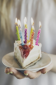 Girl holding beautiful appetizing birthday cake with many candles. Closeup. Toning.
