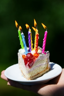 Girl holding beautiful appetizing birthday cake with many candles on green nature background. Closeup.