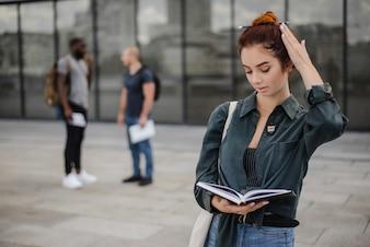 Girl holding book reading standing