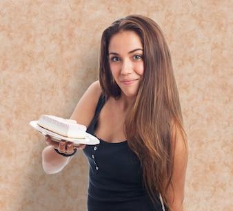 Girl holding creamy dessert on plate.