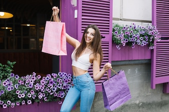 Girl holding up bags on street