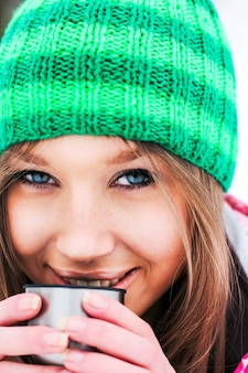 Girl in a crimson jacket and green hat drinking hot tea from a thermos in snowy mountains