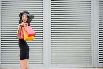 Girl in black dress carrying shopping bags
