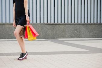 Girl in black dress standing holding bags