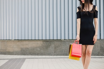 Girl in black dress standing holding bags
