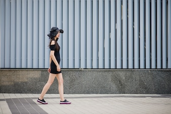 Girl in black dress walking outside