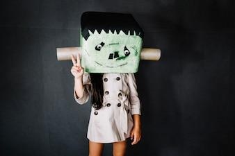 Girl in Frankenstein mask gesturing peace