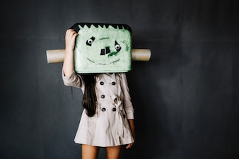 Girl in Frankenstein mask scratching her head