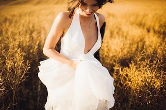 Girl in white dress running in field