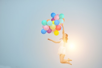 Girl jumping with balloons and sun background