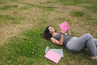 Girl lying on grass reading notebook