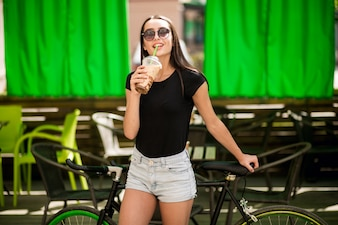 Girl on a bicycle drinking coffee