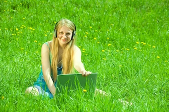 Girl  on meadow with laptop