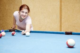 Girl playing billiards