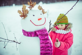 Girl playing with a snow man