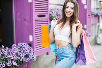 Girl posing with bags on street