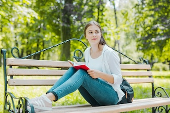 Girl posing with book on bench