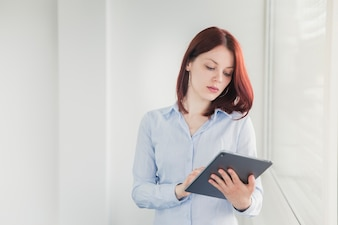 Girl posing with tablet in office