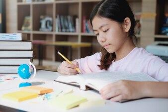 学校の図書館で読み書きする少女。