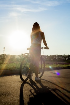Girl riding a bike at sunset